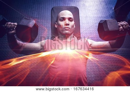 High angle view of male athlete exercising with dumbbells on weight bench in gym