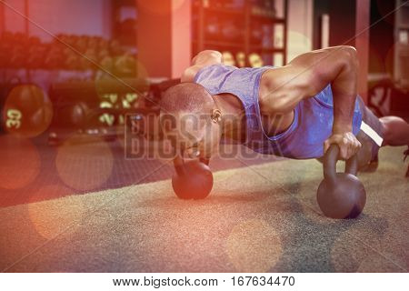 Man doing push-ups with kettlebells on carpet in fitness studio