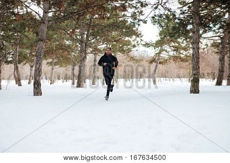 Active fitness man jogging on a snowy trail in forest winter marathon