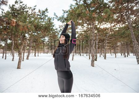 Young woman doing warming up before jogging outdoors in winter