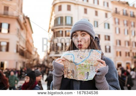 Funny playful young woman using map and having fun in the city