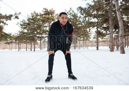 Young afro american man taking a break while doing winter fitness session
