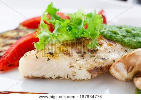 Grilled fish fillet with vegetables on a plate