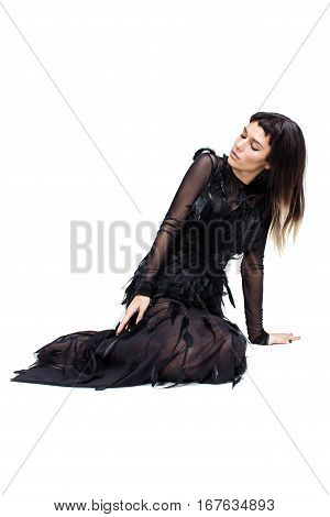 Elegant woman in studio sitting on the floor and looking down. She is wearing nice long dark diaphanous dress with a lot of feathers