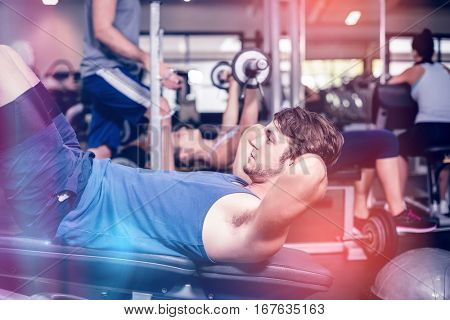 Handsome man working his abs in gym