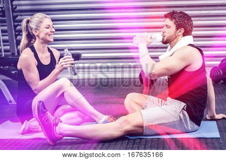 Couple sitting on fitness mat at  gym