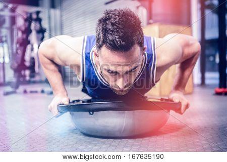 Muscular man doing push up on bosu ball at c gym