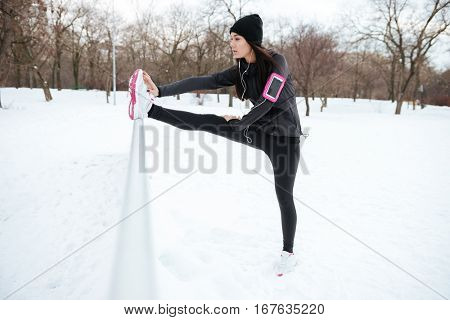 Full length portrait of a young fitness woman with armband stretching legs before running outdoors