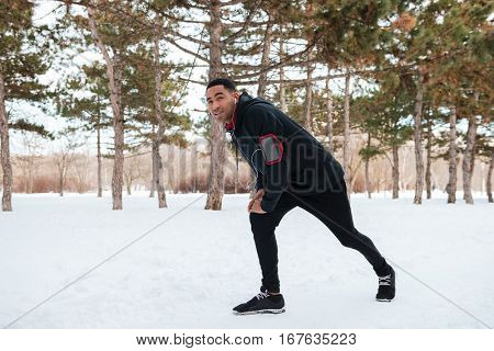 Young fitness man stretching leg muscles outdoors in winter forest
