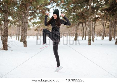Athlete young woman exercising in snowy city park