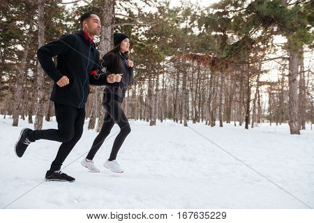 Side view of a young fitness couple running in the forest in winter