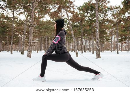 Fitness woman runner stretching legs before workout outdoors in winter forest