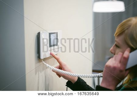 Blonde Woman Answers The Intercom Call While Holding The Phone To Your Ear