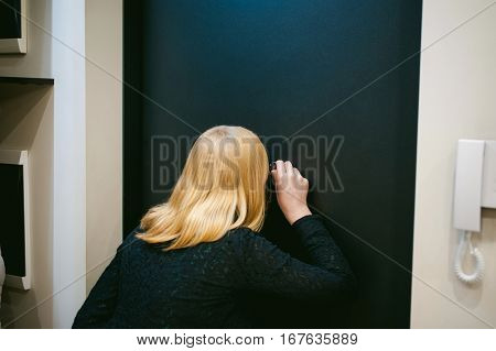 Blonde Woman Looks Through The Peephole While In His Apartment, Waiting For The Arrival Of Guests