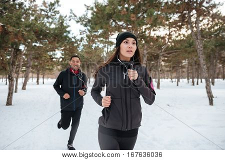 Young fitness couple running outdoors on a winter day