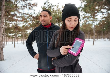 Young multiracial sports couple getting ready for running marathon in winter forest