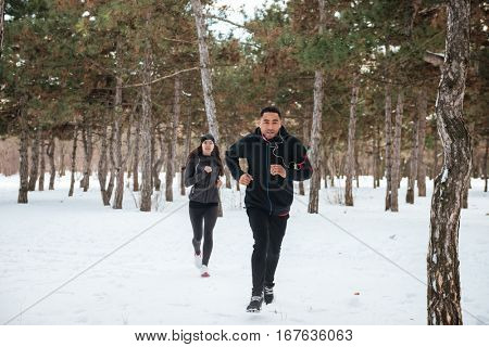Happy young couple doing fit cross in the forest in winter