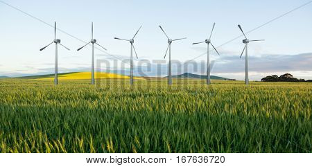 Digital composite image of wind turbines against green wheat field