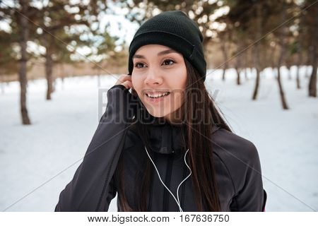 Close up portrait of a sportswoman in hat listening music with earphones outdoors
