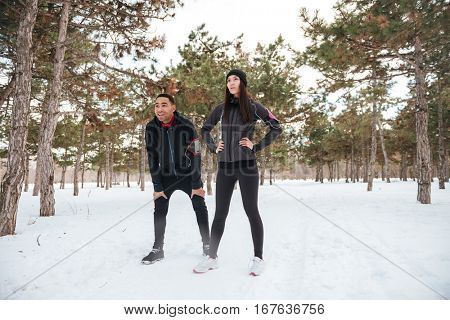 Young fitness couple having break after running in winter forest