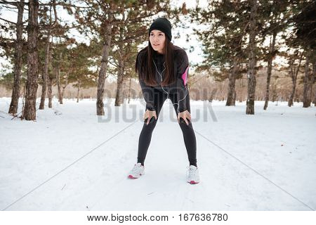 Female athlete exercising outside in cold weather on forest path wearing activewear