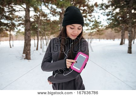 Portrait of a lovely young fitness woman with armband and earphones outdoors