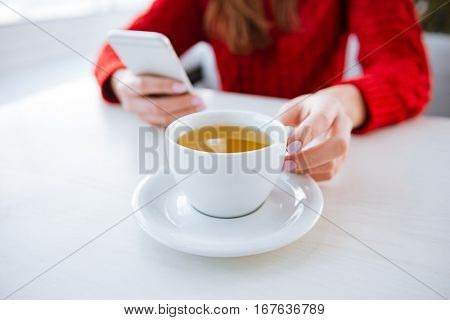 Cropped image of attractive young lady sitting in cafe at cold winter day and using phone while holding cup of tea. Focus on cup.
