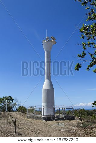 Lighthouse and blue sky Apo island Philippines. Modern lighthouse on hill under sun. Sunny island's empty lighthouse. Abandoned lighthouse on a desert island. Lighthouse on top of mountain