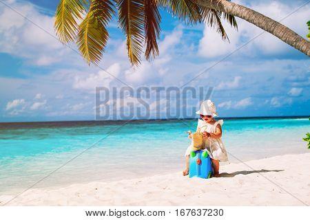 cute little girl travel on summer tropical beach