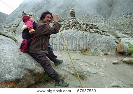 Ngari, Tibet, China - August 2010: Tibetan pilgrim carries baby  traditional bypass around of Sacred Mount Kailash on altitude at 5,500 meters above sea level. on August 2010 in Ngari, Tibet, China.