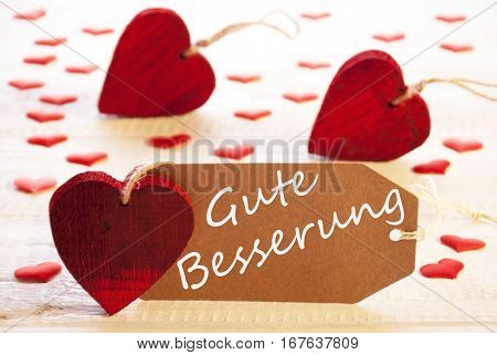 Label With German Text Gute Besserung Means Get Well. Many Red Heart. Wooden Rustic Or Vintage Background.