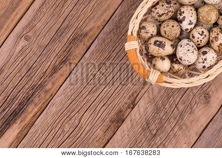 Quail eggs in a basket on old wooden table. Top view.
