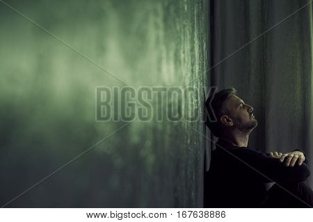 Depressed man sitting alone in gloomy room poster