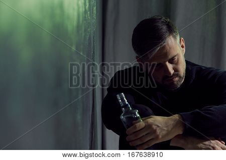 Alcohol addicted man sitting alone with alcohol bottle poster