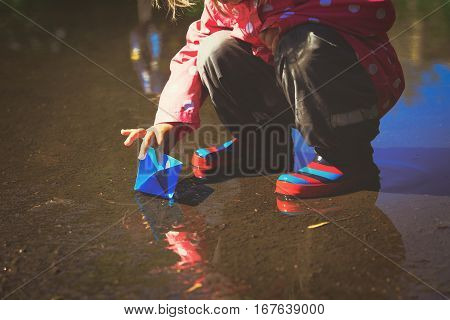 little girl playing with paper boats in puddle, kids seasonal activities