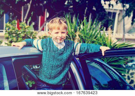 happy blond little boy enjoy travel by car in city