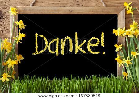Blackboard With German Text Danke Means Thank You. Spring Flowers Nacissus Or Daffodil With Grass. Rustic Aged Wooden Background.
