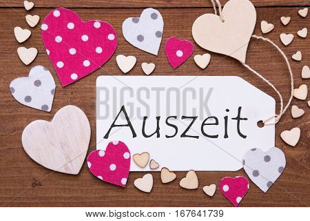 One Label With German Text Auszeit Means Downtime. Flat Lay View With Wooden Vintage Background. Pink Wooden And Paper Hearts.