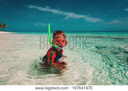happy little boy swimming with mask at sea beach