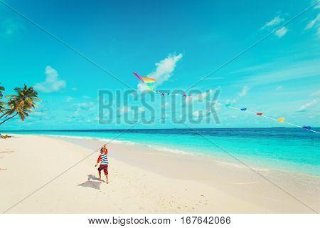 Little boy flying a kite on tropical beach, beach activities