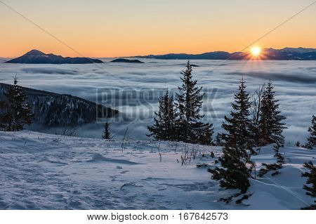 First Sunrays On Mountains Above Low Clouds