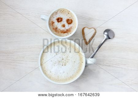 cheerful snowman of two coffee mugs with frothy cappuccino top view / happy appetite