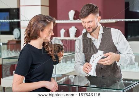 Jeweler brunette man presenting, showing and talking about of golden necklace with blue stones for brunette girl with wavy hair. Looking each other and smiling. Buyer choosing jewelry in luxury store.