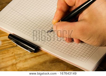 Male hand writing using fountain pen on the notebook