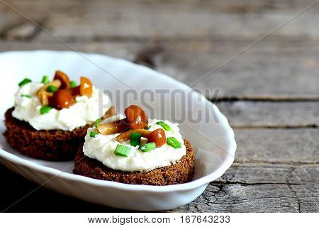 Canape with cottage cheese, mushrooms and green onion on a plate on a wooden background with copy space for text. Canape made from rye bread, soft cheese and canned mushrooms. Closeup