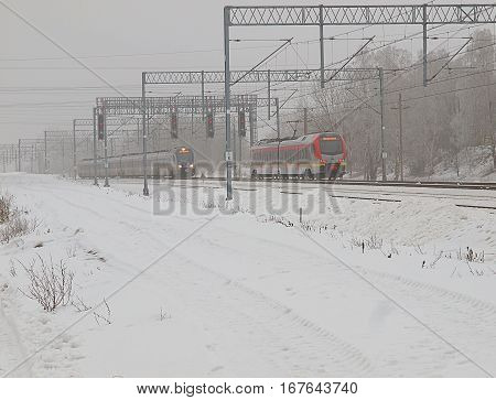 Winter turnout. Lodz, Poland - January 26, 2017 Modern passenger train from Lodz, passes standing under the red light queue electricity.