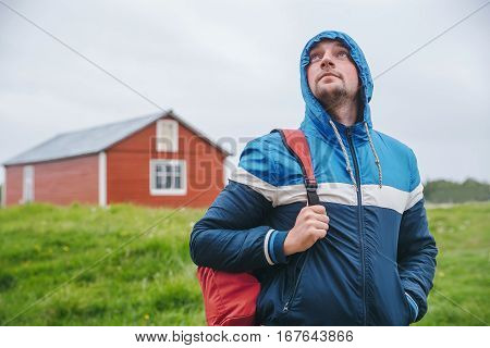 Tourist with a backpack in blue jacket on background of green field