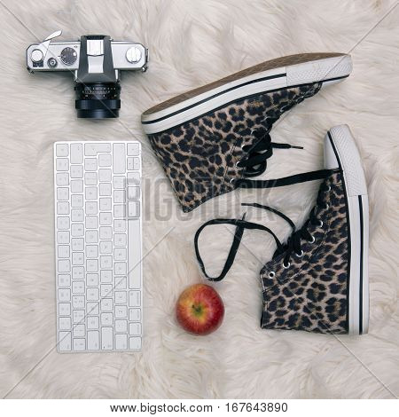 Lifestyle Flat Lay with leopard print boots old camera keyboard and apple on a fur rug