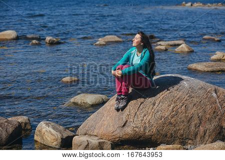 Tourist girl sitting on a rock against the sea