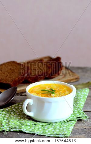 Chicken rice soup with vegetables in a bowl. Bread slices, textile napkin, spoon on wooden table. Homemade chicken rice soup recipe. Vertical photo. Closeup
